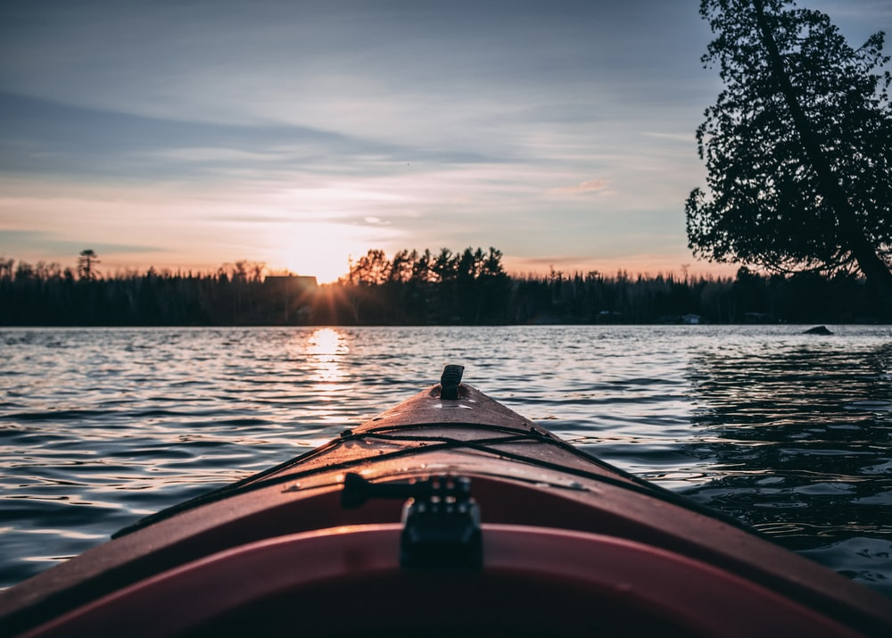 person riding on boat on lake during sunset