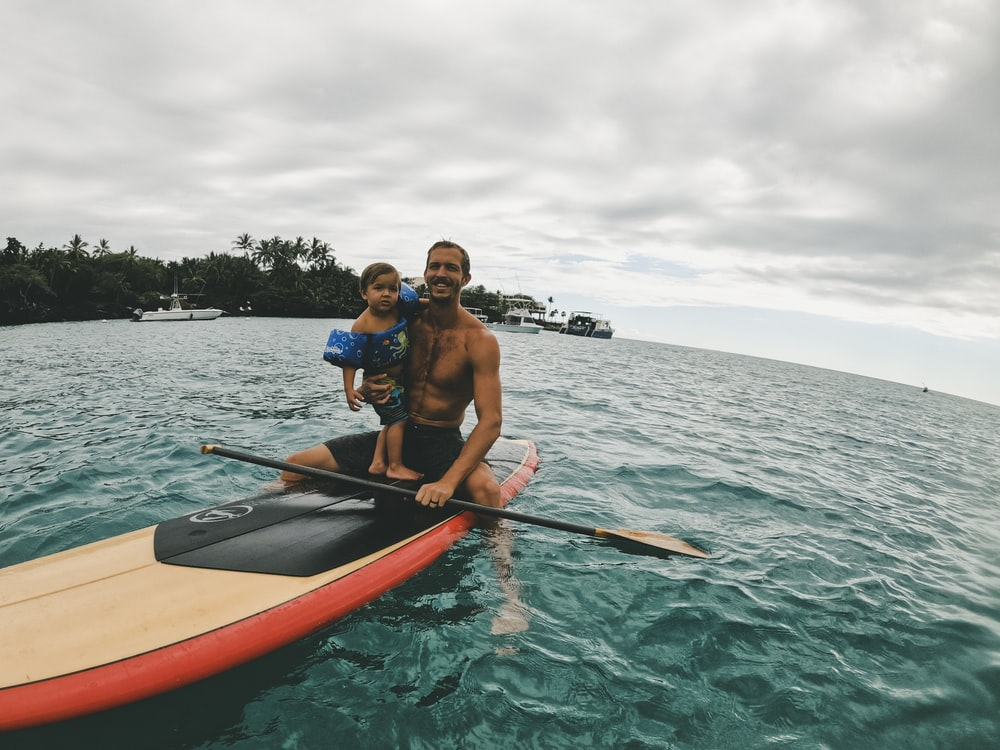 2 men riding on orange kayak on sea during daytime