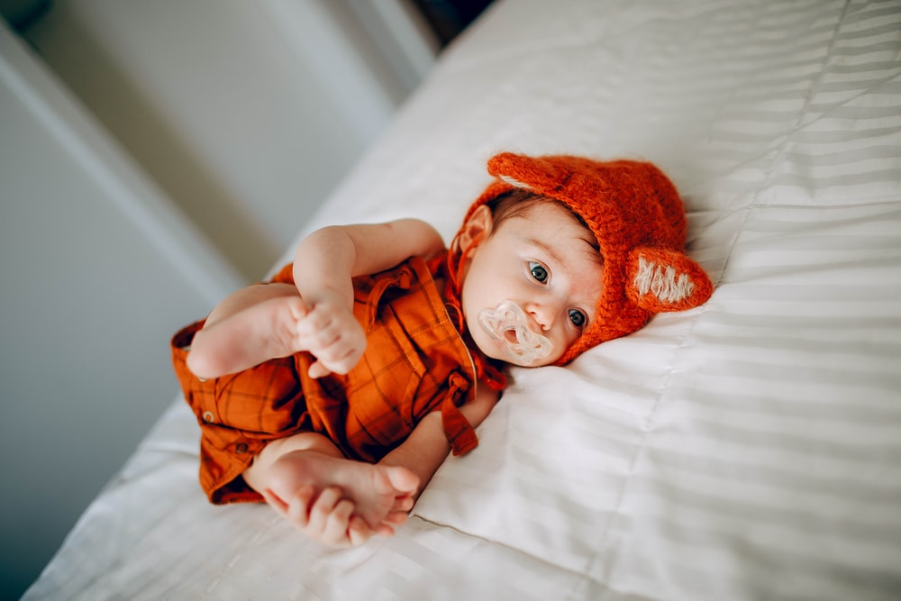 baby in orange knit cap lying on white bed