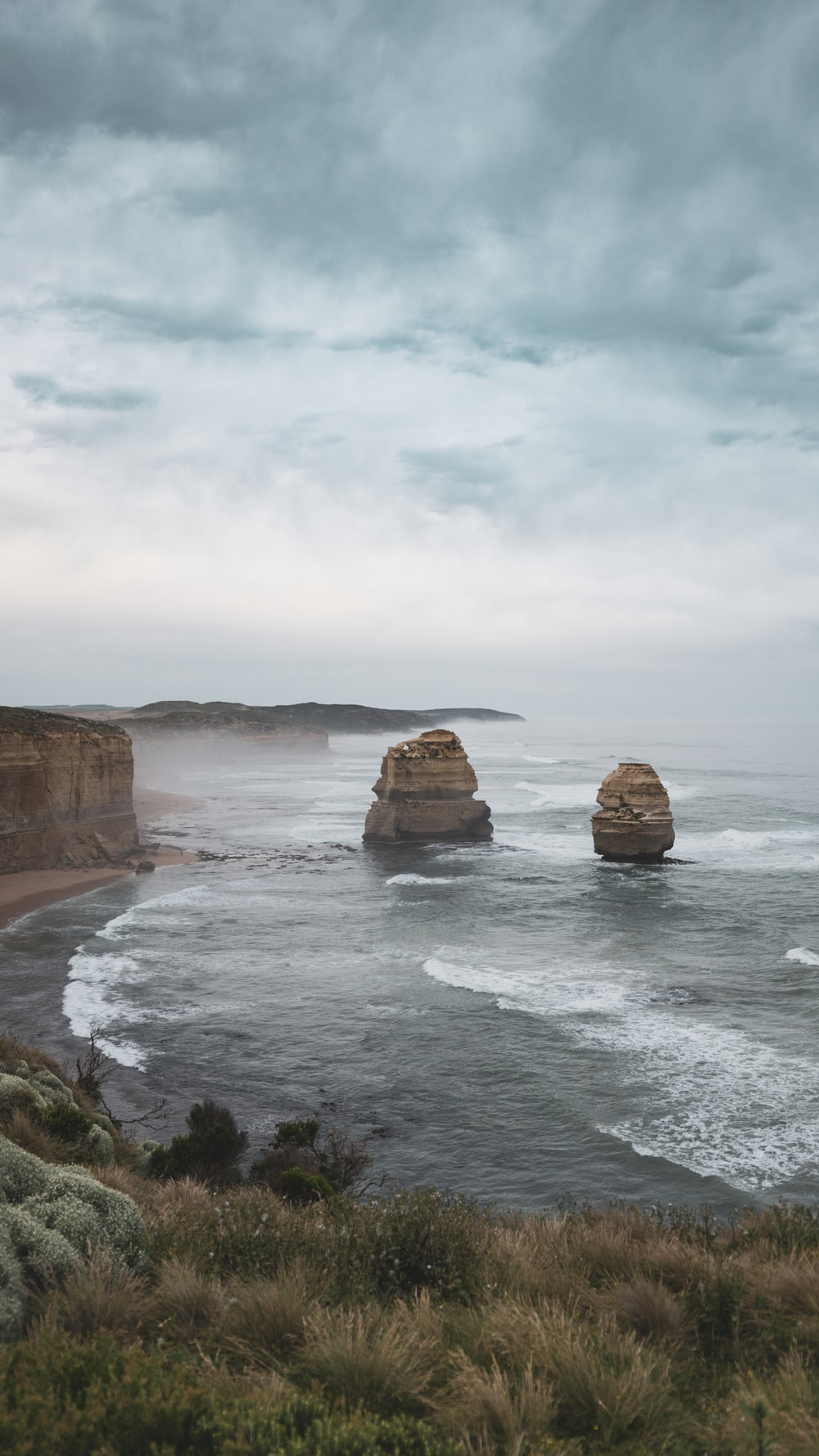 brown rock formation on sea under white clouds during daytime
