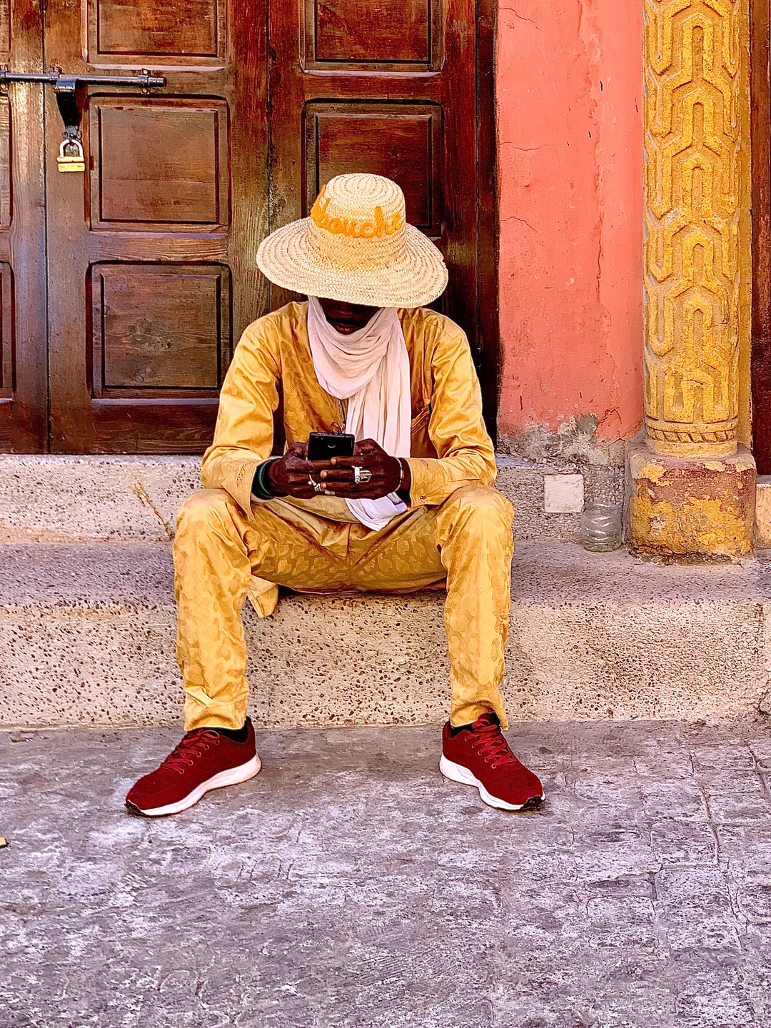 Golden Guy of Marrakech sitting in front of an old ancient wooden door or portal of a Riad in the Médina.
