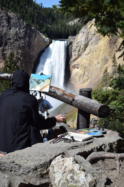 man in black jacket sitting on brown wooden bench near waterfalls during daytime