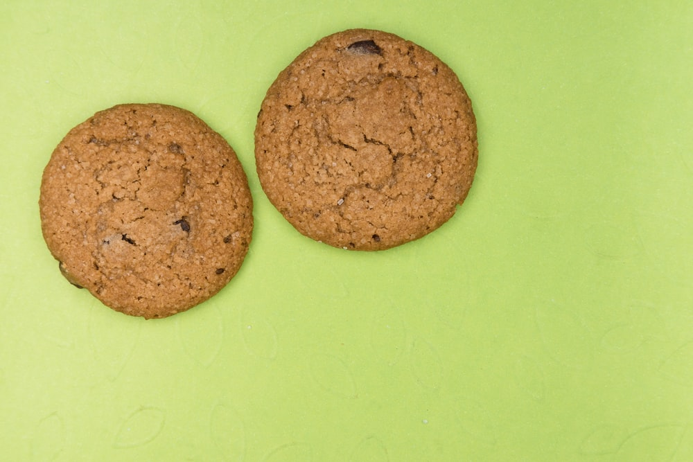 two brown cookies on green surface