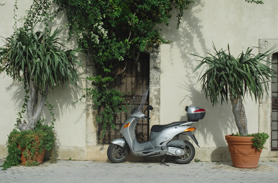 A grey scooter parked outside an old house.