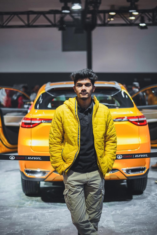man in yellow zip up jacket standing beside orange car