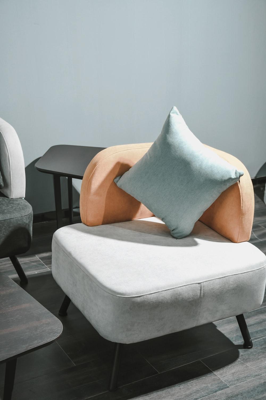 white and brown throw pillow on white sofa chair