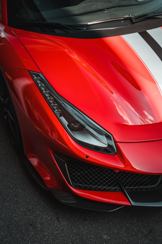 red ferrari car on black asphalt road
