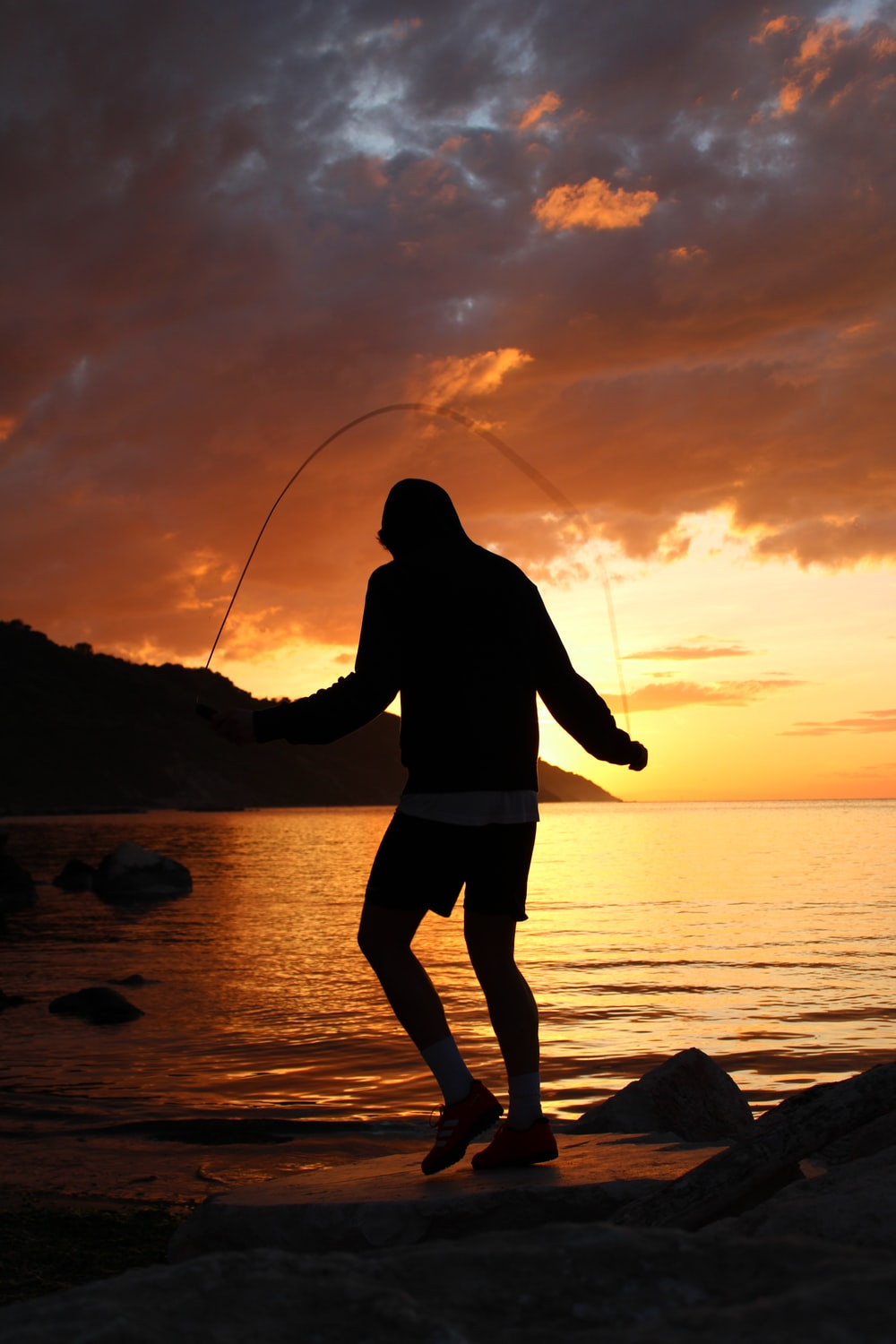 silhouette of man holding fishing rod standing on seashore during sunset