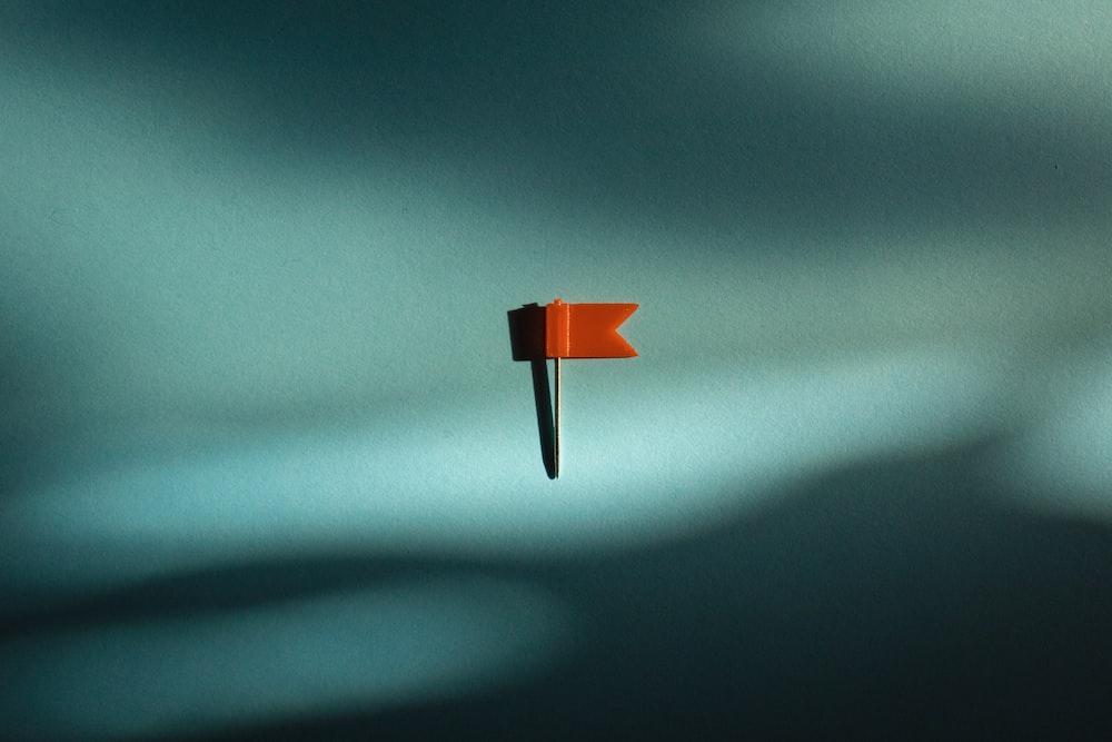 orange and black umbrella on white surface