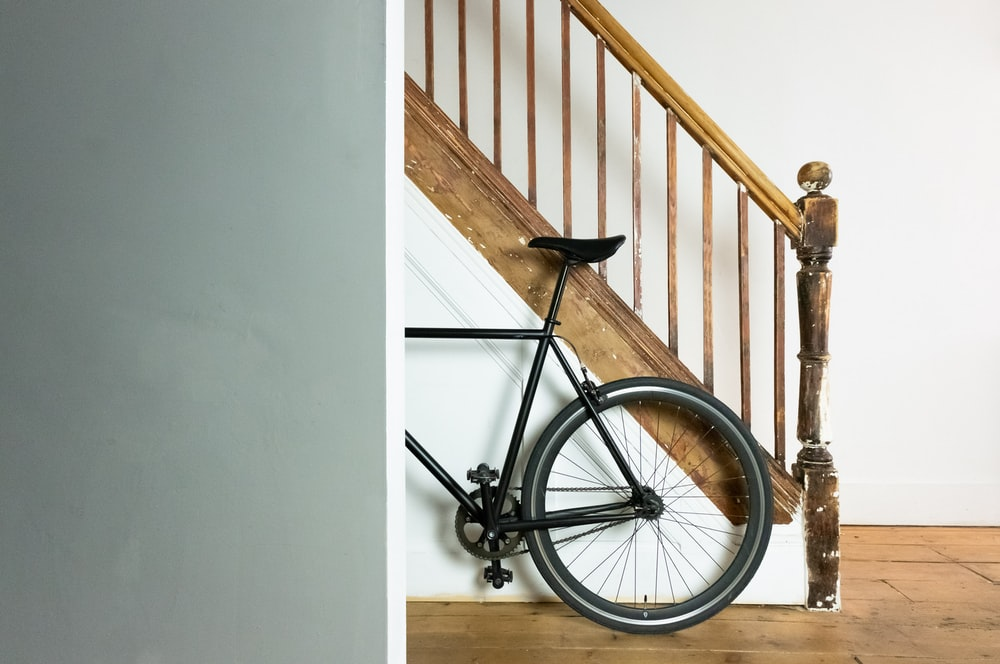 black and gray bicycle leaning on white wall