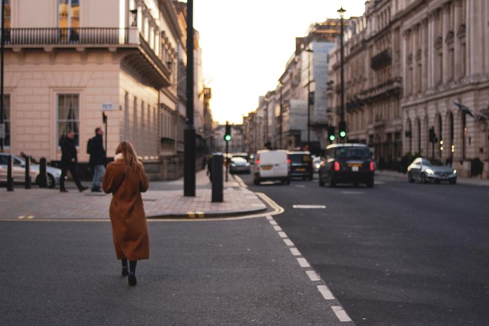 woman in brown coat walking on pedestrian lane during daytime