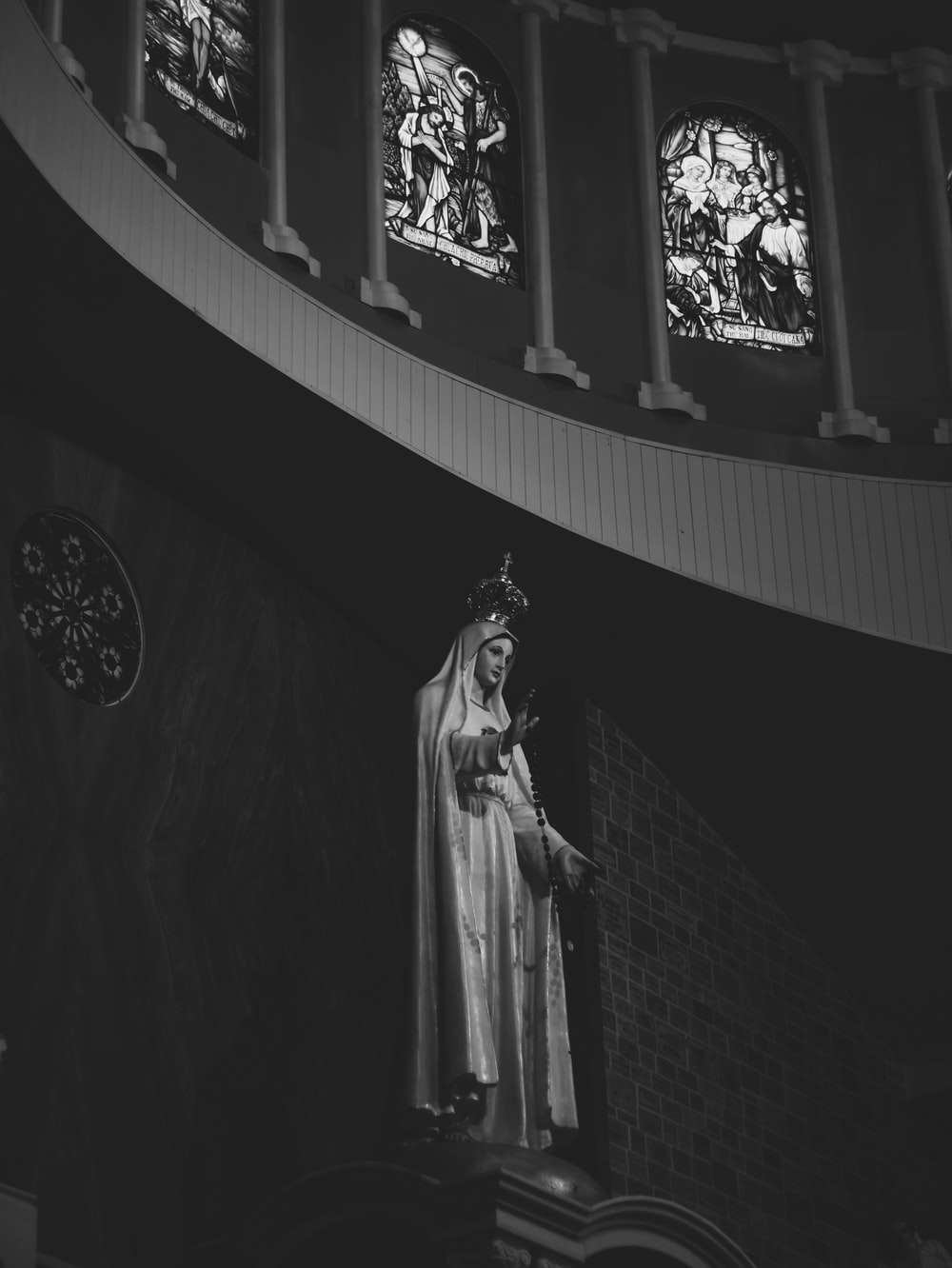 grayscale photo of woman in dress statue