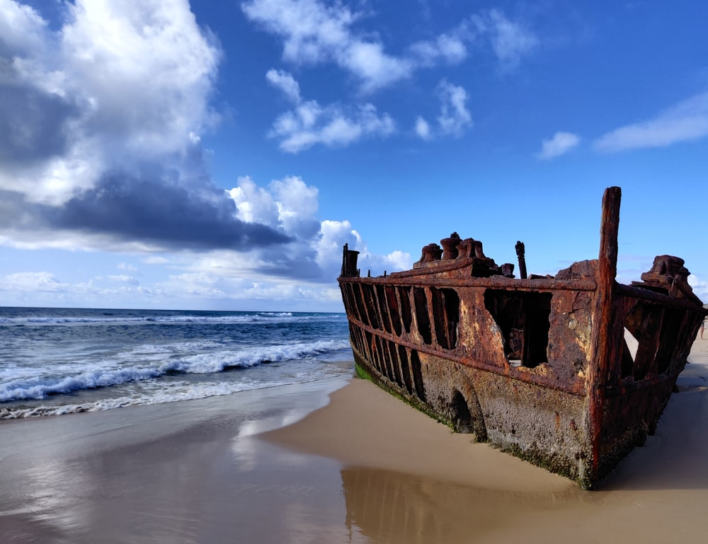 brown wooden ship on sea shore under blue sky and white clouds during daytime