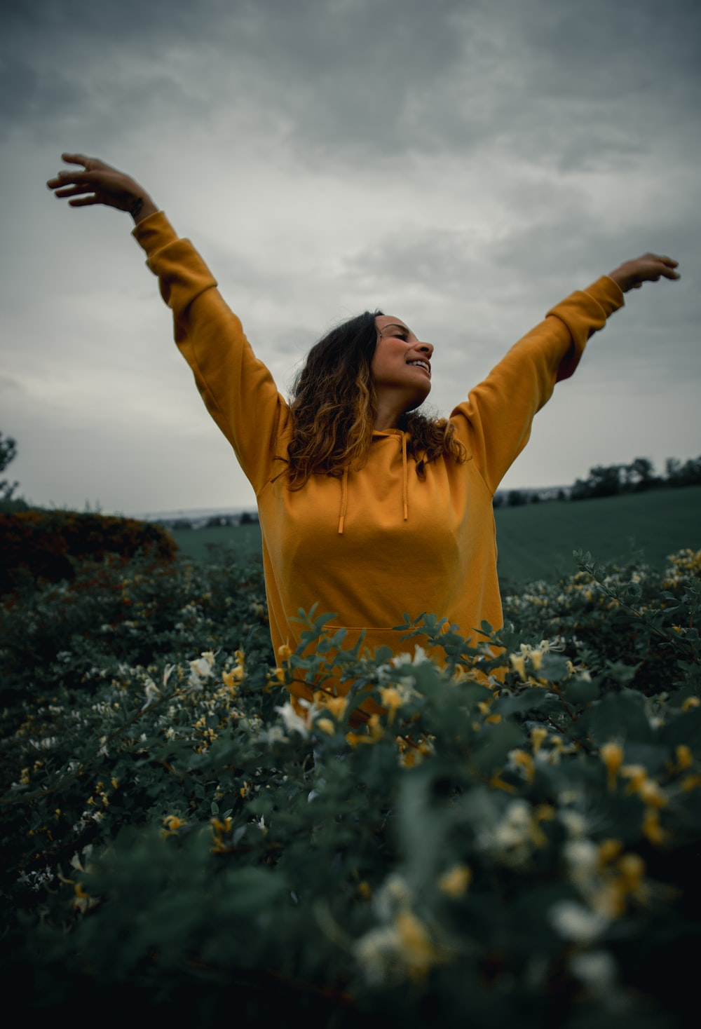 woman in yellow long sleeve shirt standing on flower field during daytime