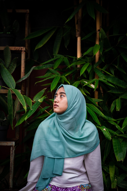 woman in teal hijab standing near green plants