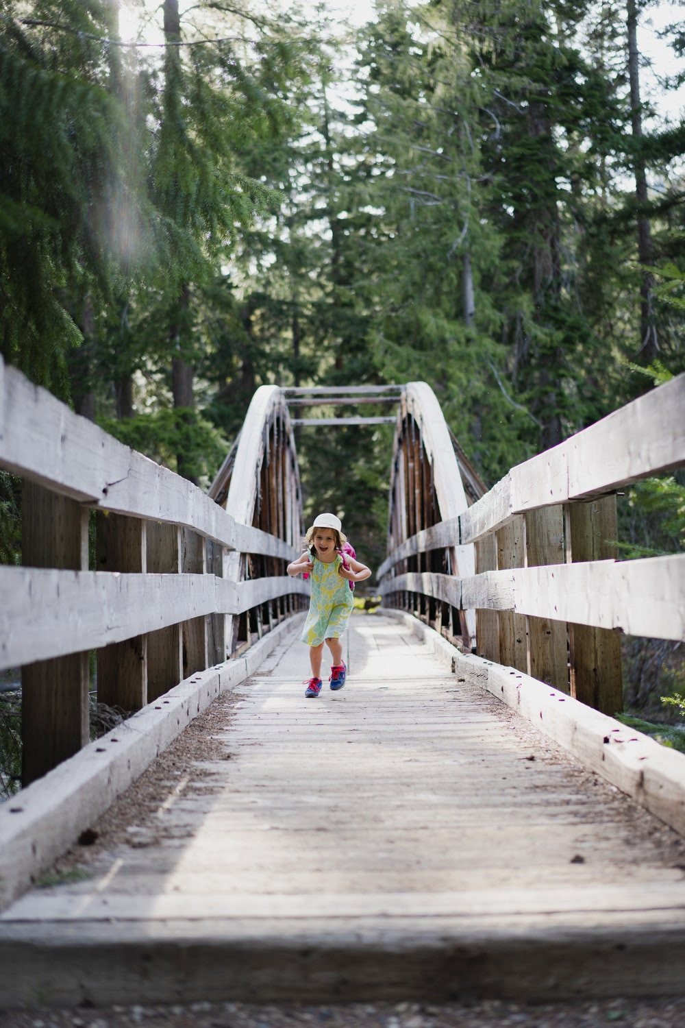girl in green jacket walking on wooden bridge