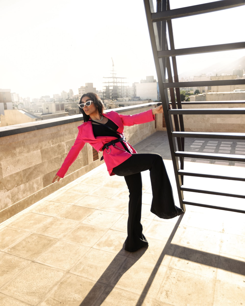 woman in red long sleeve shirt and black pants standing on brown concrete stairs