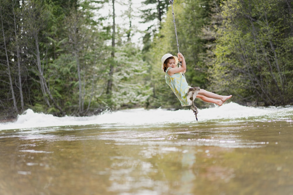 boy in green t-shirt and brown shorts riding on swing over river during daytime
