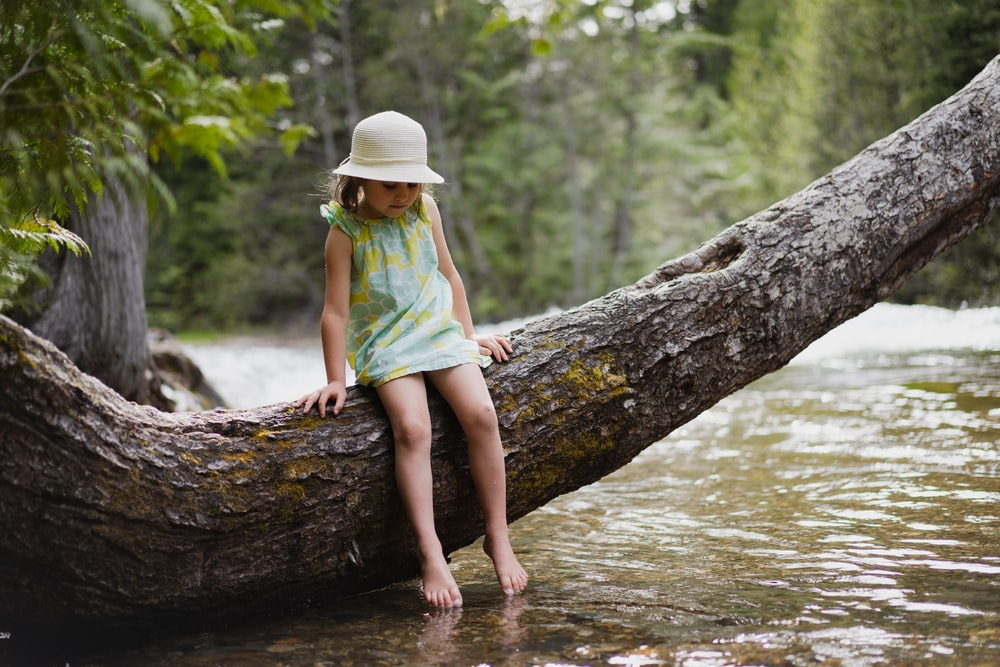 girl in green shirt and brown hat sitting on tree log in river during daytime