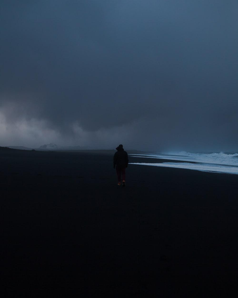 man in black jacket walking on black sand under gray cloudy sky