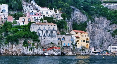 white and brown concrete houses near body of water during daytime amalfi coast zoom background