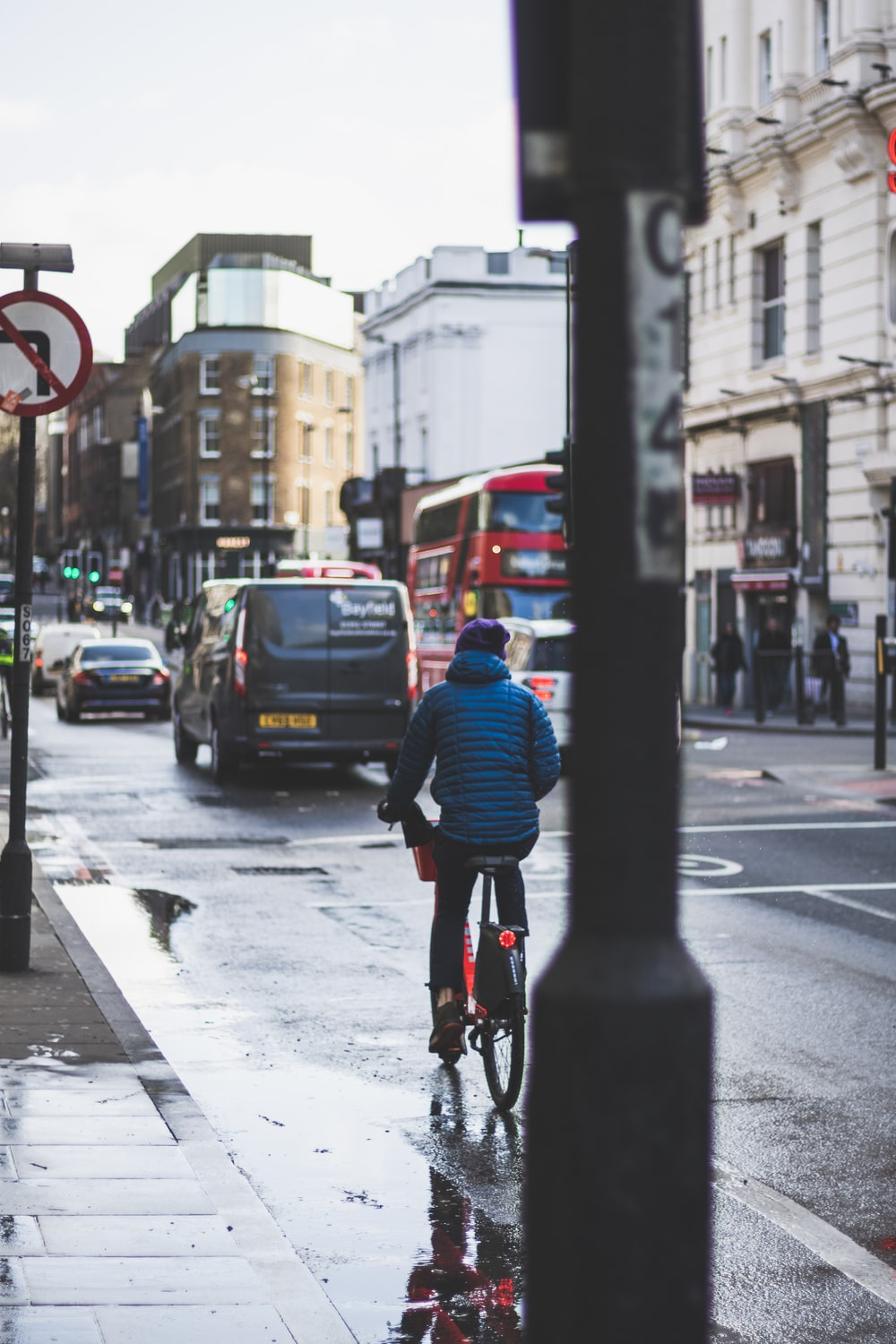 man in blue jacket riding bicycle on road during daytime