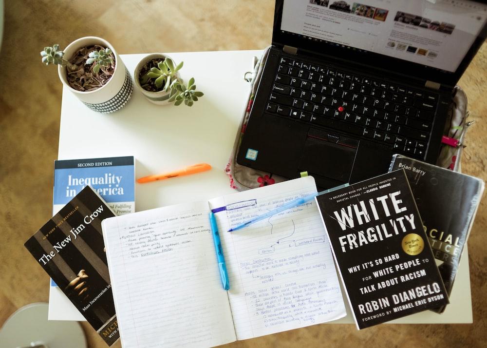 black laptop computer beside white printer paper