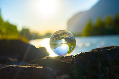 A Glass ball surrounded by nature. In the back you can see the river called Inn.