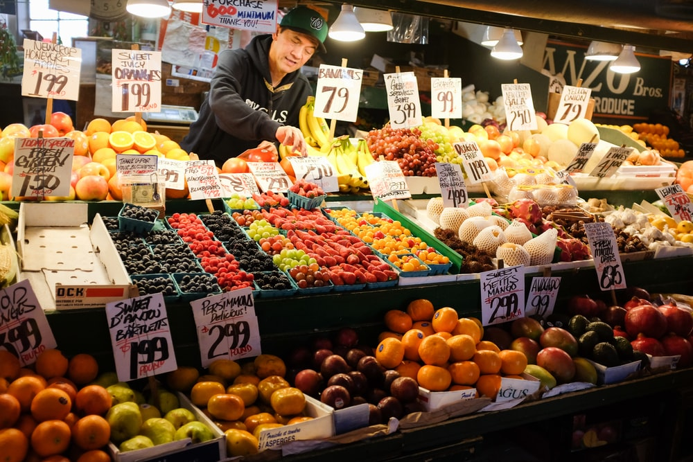 man in black jacket standing in front of fruit stand