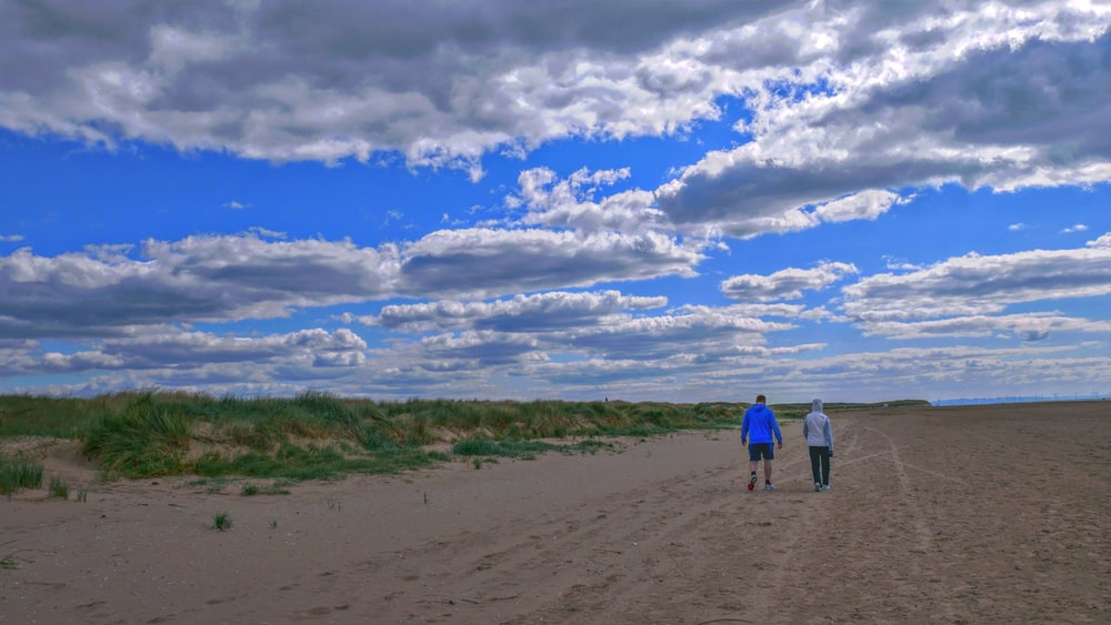 2 men walking on brown sand under blue sky and white clouds during daytime