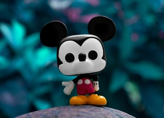 mickey mouse plush toy on gray rock