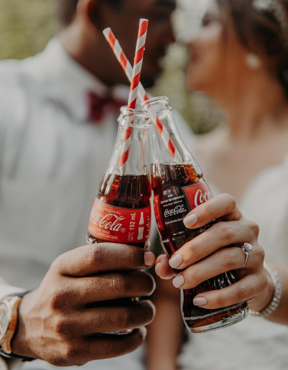 person holding coca cola bottle
