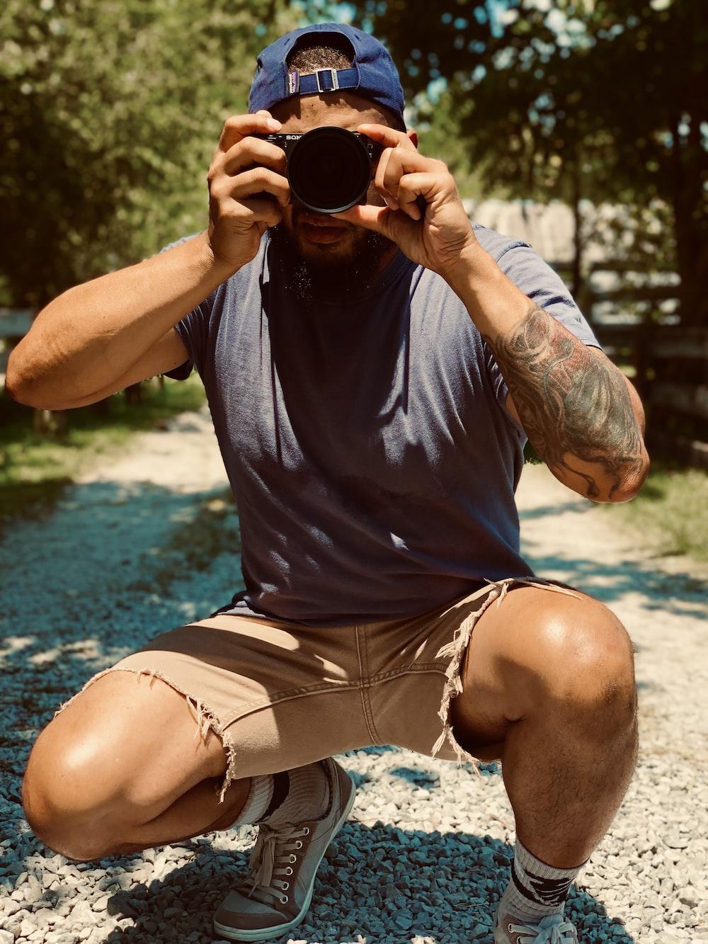 man in black crew neck t-shirt and white shorts drinking from black ceramic mug