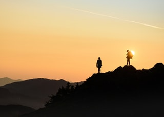 silhouette of person standing on rock formation during sunset