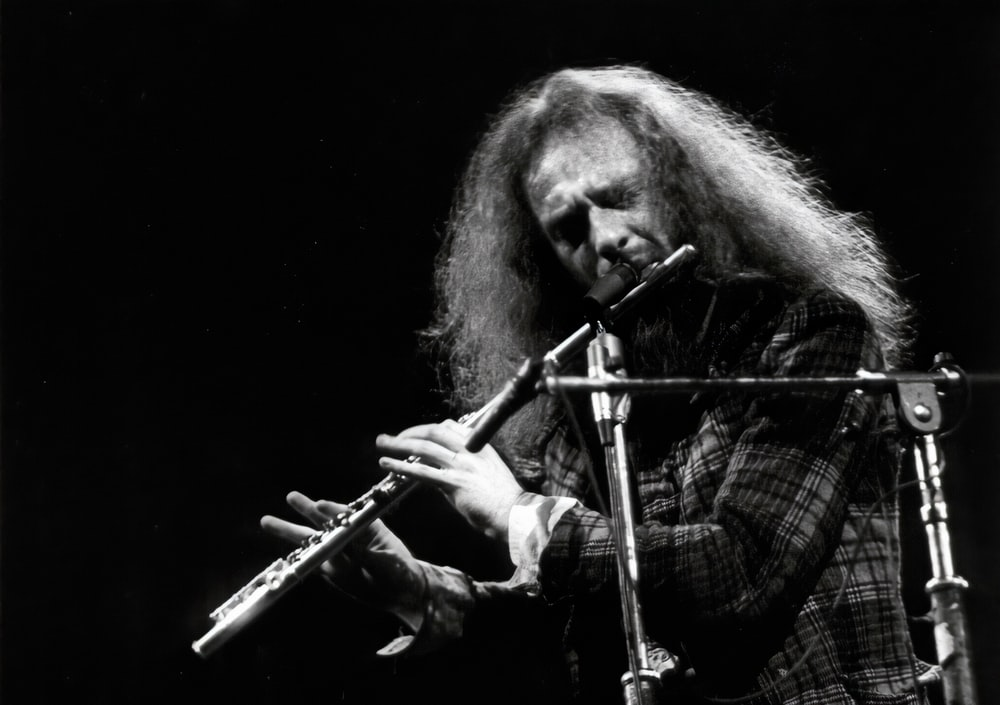 man in plaid shirt playing flute