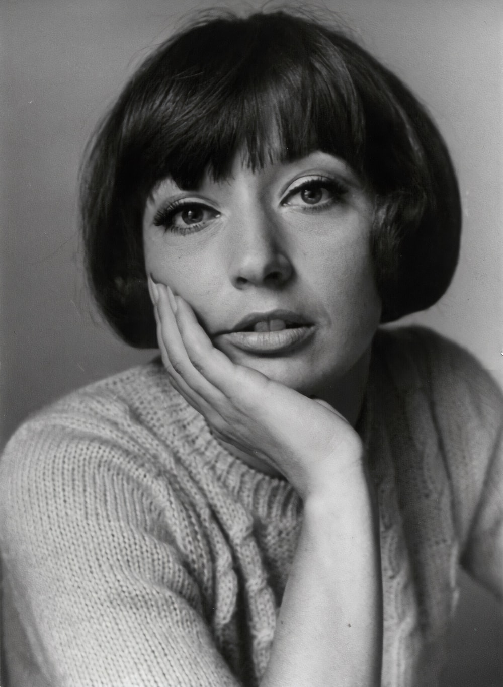 woman in sweater with hand on face