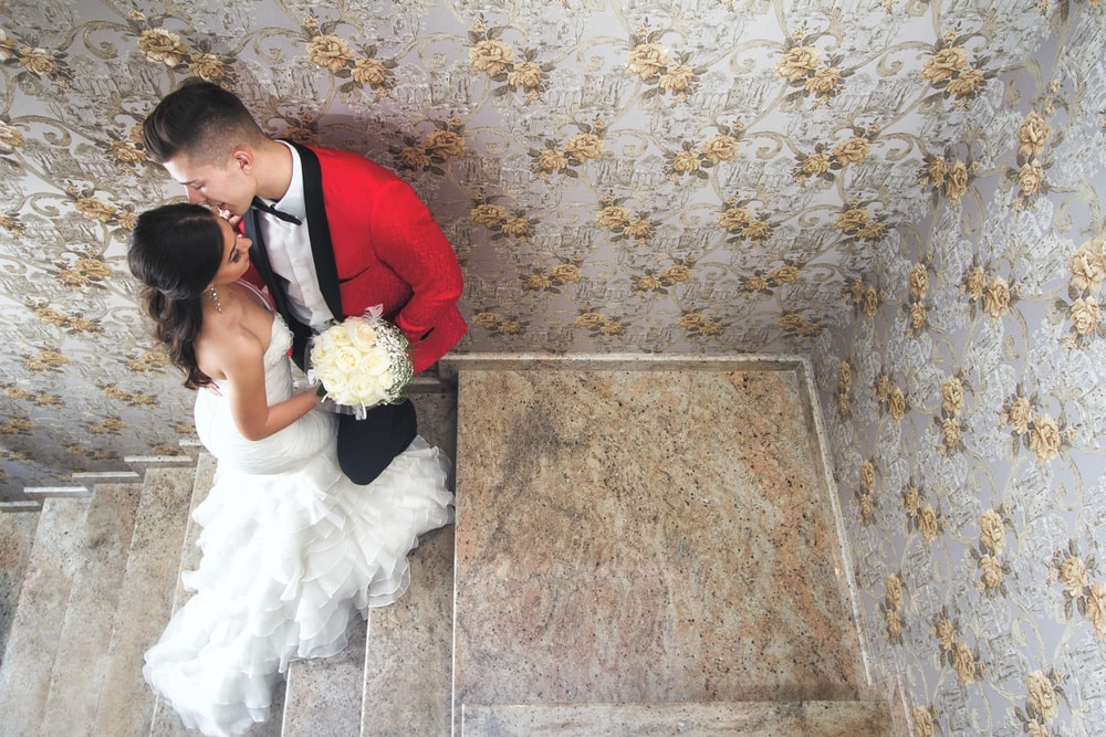 man in red suit kissing woman in white wedding dress
