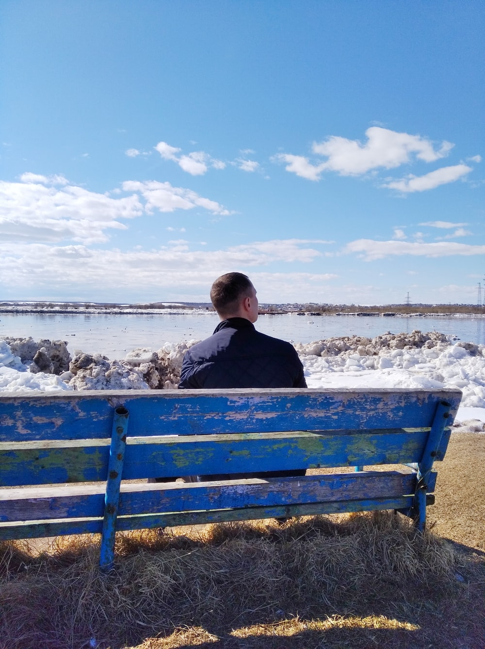 man in black jacket sitting on blue wooden bench during daytime