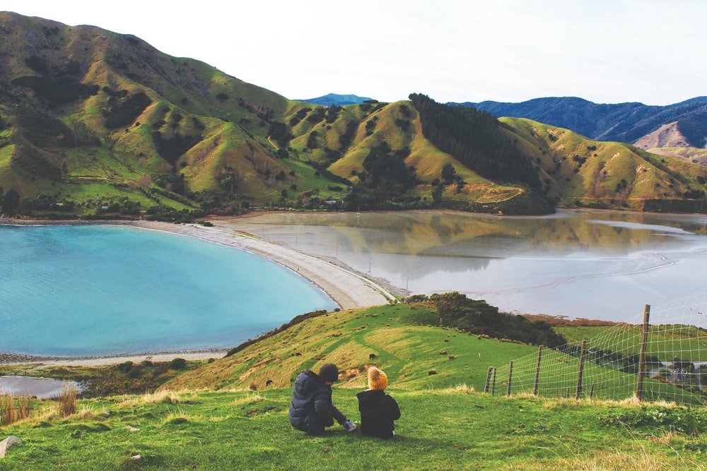 man and woman sitting on grass field near lake during daytime