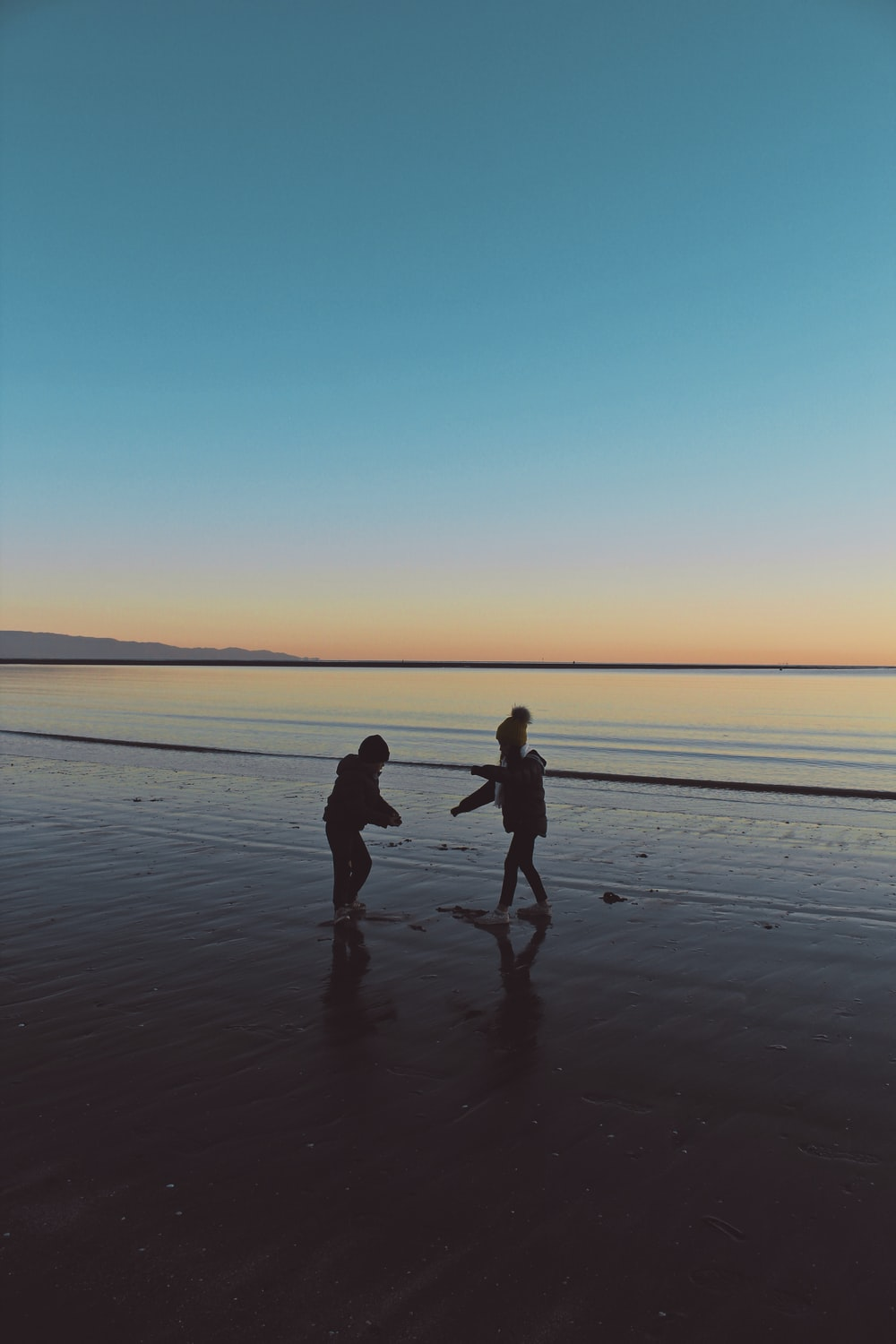 man and woman walking on beach during sunset