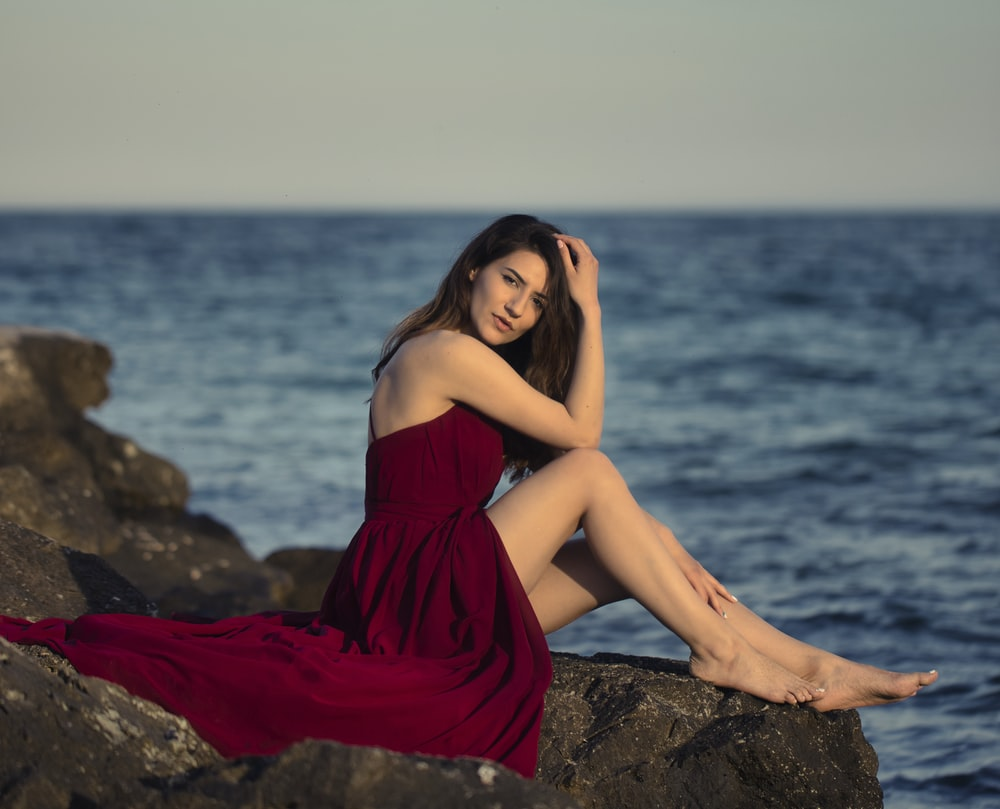 woman in red dress sitting on rock near sea during daytime