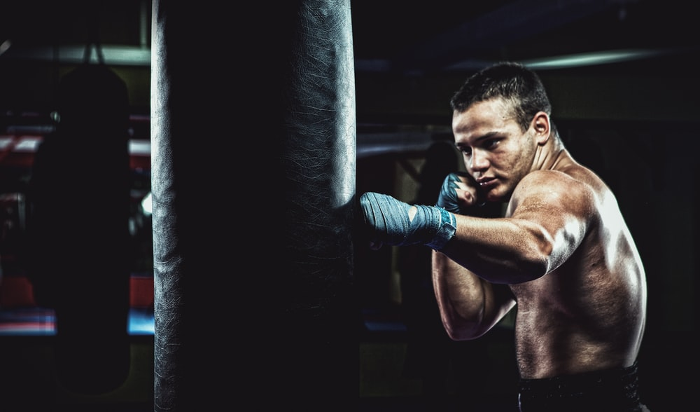 man in blue pants and black boxing gloves