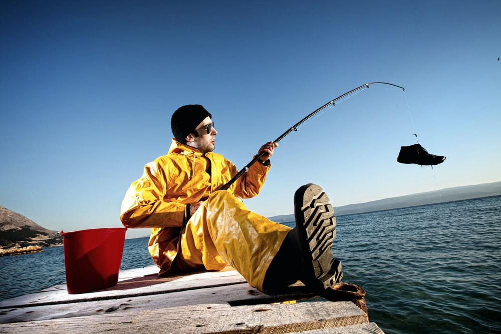 man in yellow jacket and black and white adidas cap holding black fishing rod