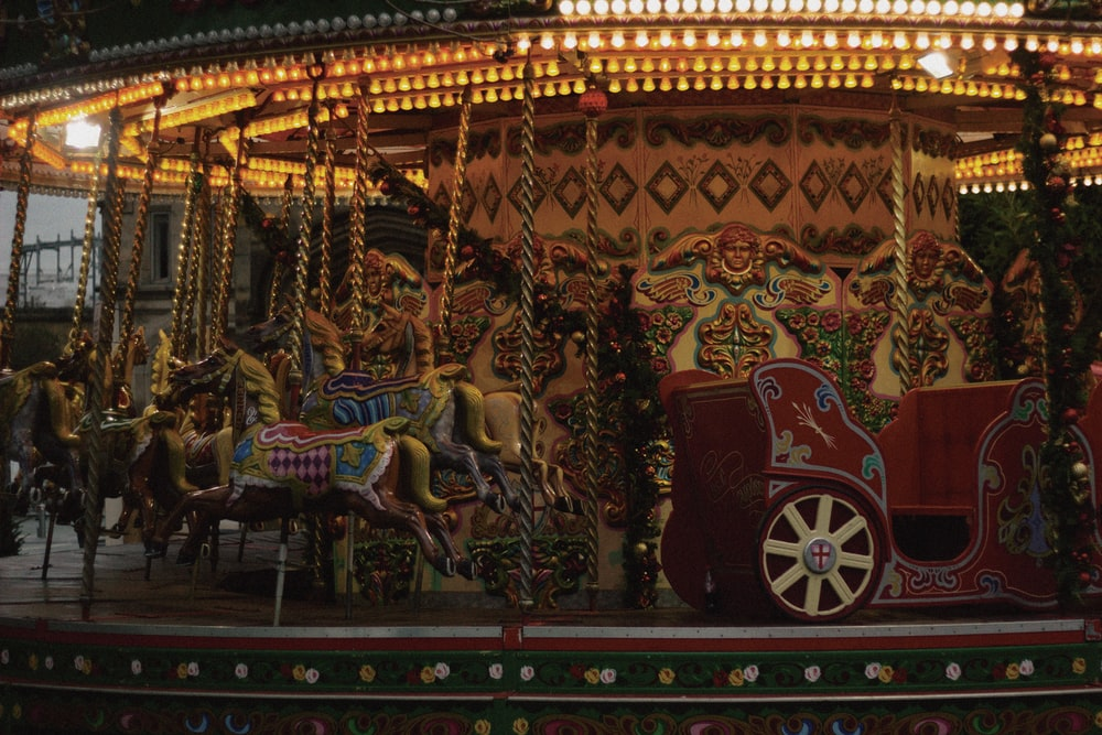 red and gold carousel with people riding