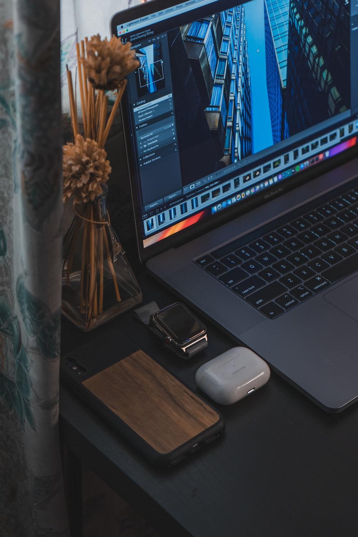 macbook pro beside black smartphone on brown wooden table
