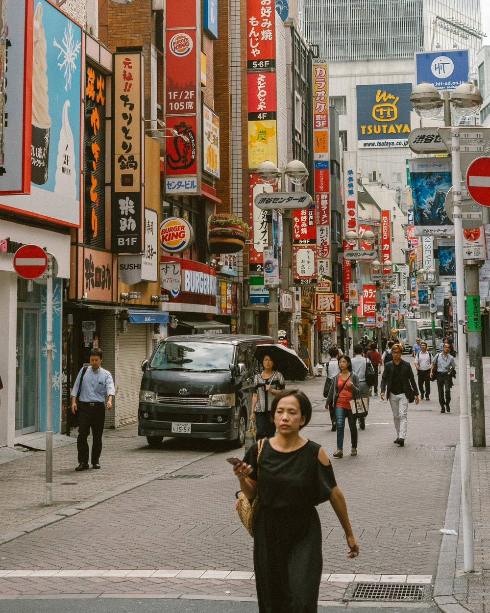 man in black crew neck t-shirt walking on sidewalk during daytime