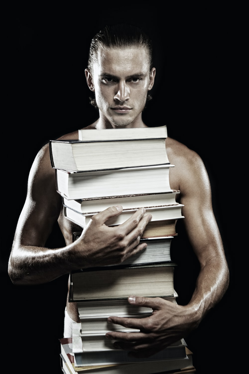 man holding books with black background