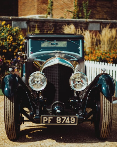 blue vintage car near white wooden fence during daytime
