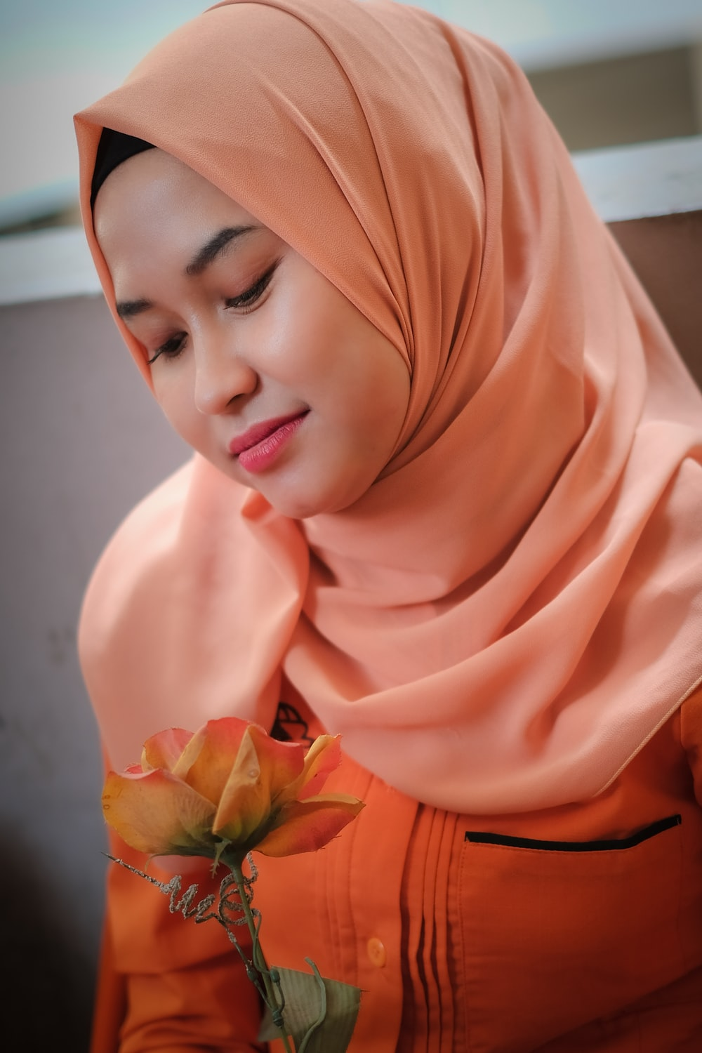 woman in orange hijab holding green flower