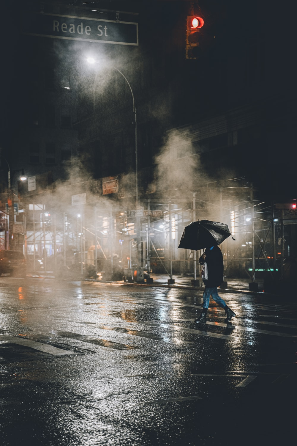 person in black jacket holding umbrella walking on street during rainy day
